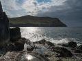 Vagues de l'Atlantique au pied des falaises ; au loin, l'île de Dursey.